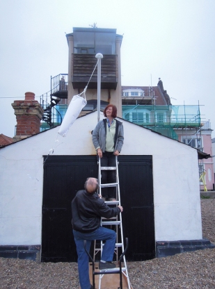 Jane Oldfield installing her Windsock piece on the flag pole